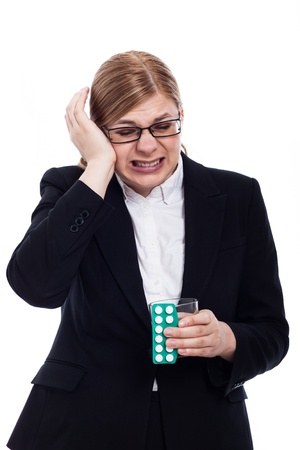 Businesswoman with migraine holding painkillers and glass of water, isolated on white background. photo