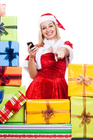 Happy woman in Christmas costume holding phone and pointing at you, isolated on white background. photo
