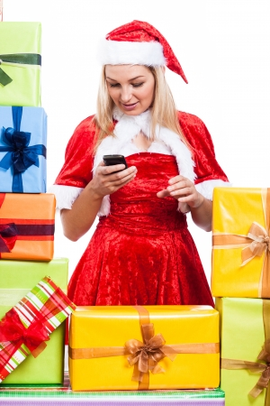 Christmas Woman texting message with phone surrounded by presents, isolated on white background. photo