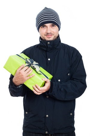 man carrying box: Friendly man in winter jacket holding green present, isolated on white background. Stock Photo