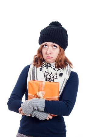 Unhappy winter woman holding present and looking up, isolated on white background. photo