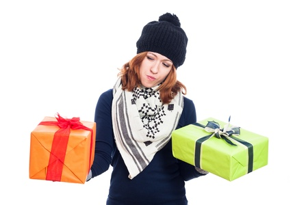 indecisive: Indecisive winter woman holding two presents, isolated on white background.