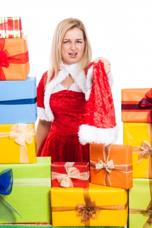 Angry Christmas woman holding Santa hat, surrounded by presents, isolated on white background. photo