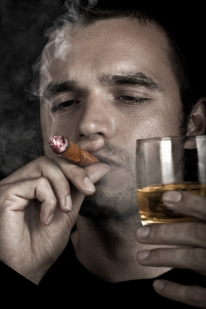 Dark dramatic photo of a man smoking cigar and holding glass of whiskey. photo
