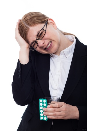 painkillers: Businesswoman with headache holding painkillers and glass of water, isolated on white background.