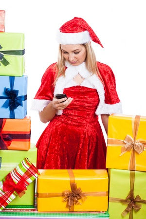 Christmas Woman texting message on phone surrounded by presents, isolated on white background. photo