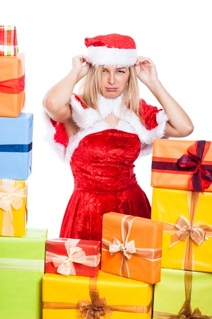 Annoyed Christmas woman in Santa costume, surrounded by presents, isolated on white background. photo