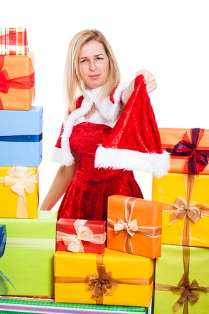 Frowning Christmas woman holding Santa hat, surrounded by presents, isolated on white background. photo