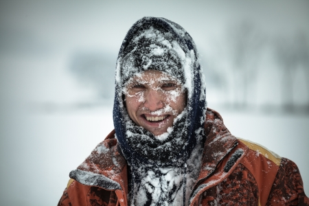 expeditions: Happy man covered by snow enjoying winter.