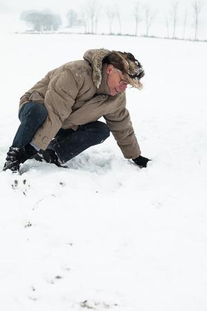 lesionado: Hombre mayor con la pierna lesionada en la nieve.
