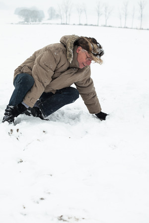 snow break: Senior man with injured leg on snow.