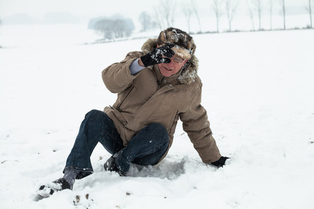 snow break: Senior man accident falling on snow in winter. Stock Photo
