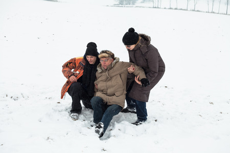 Couple of young people helping to senior man stand up after accident on snow.