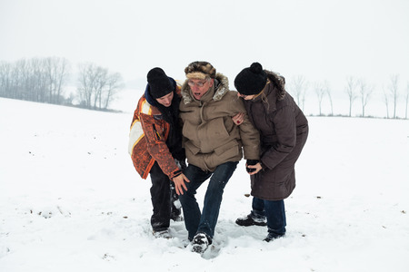 Couple of young people helping to senior man stand up after accident on snow in winter.