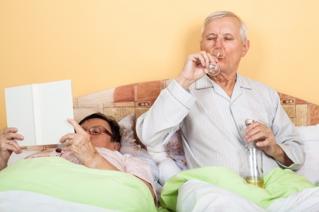 Retired couple relaxing in bed with alcohol and book photo