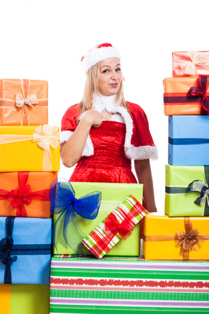 Christmas woman surrounded by presents pointing at herself, isolated on white background. photo
