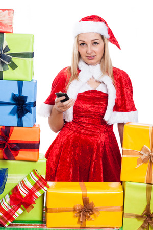 Christmas Woman holding mobile phone surrounded by presents, isolated on white background. photo