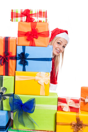 Smiling Christmas woman hiding behind many presents, isolated on white background. photo