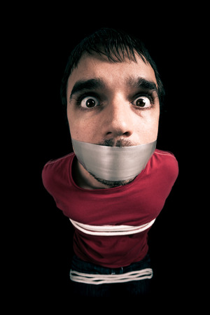 censorship: Kidnapped man hostage with tape over mouth and tied up with rope Stock Photo