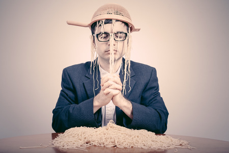 Pastafarian wearing a colander praying for pasta to the Flying Spaghetti Monster. photo