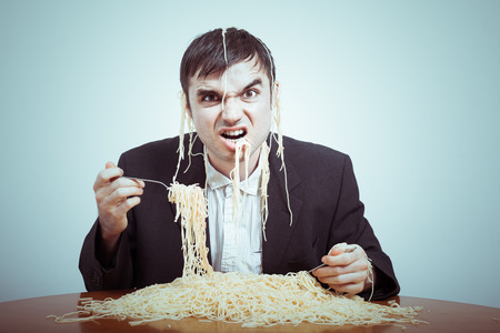 consumerist: Greedy consumerism concept. Nasty businessman eating pasta on the table. Stock Photo