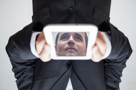 Portrait of upside down businessman with reflected face in digital tablet. photo
