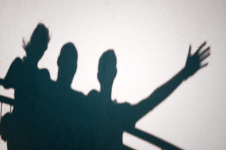 Creative photo of three people shadows on white wall gesturing photo
