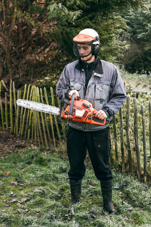 forestry industry: Portrait of professional gardener with chainsaw standing in the garden.