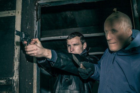 armed: Two dangerous armed men pointing with weapons and standing in old dark cabin. Stock Photo