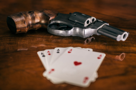 Risky gambling concept. Gun and four aces cards on wooden table. photo