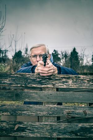criminal defense: Senior man aiming a gun at you and hiding behind barricade outdoors.
