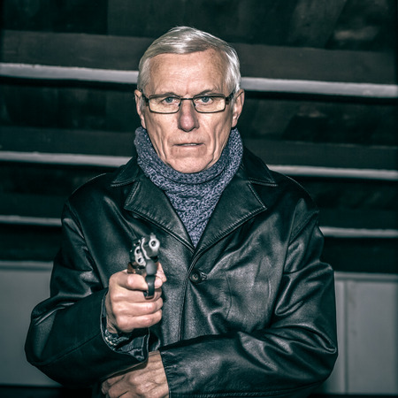 Portrait of dangerous senior man aiming a gun at you. photo