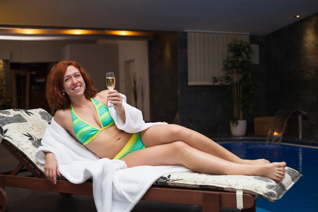 Woman with glass of wine enjoying wellness and spa swimming pool. photo
