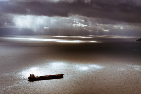 Dramatic dark moody sky and Mediterranean Sea landscape with ship leaving Gibraltar harbor. photo