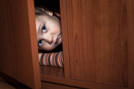 Scared child boy hiding in wardrobe photo