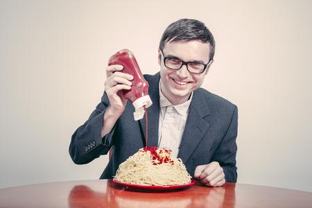 Concept de consumérisme positif. Homme d'affaires heureux de verser le ketchup sur un grand plat de pâtes.