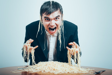 consumerist: Crazy consumerism concept. Mad nasty businessman eating pasta on the table.