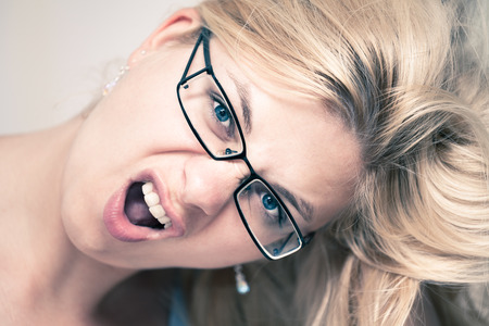 angry blonde: Closeup of excited woman face.