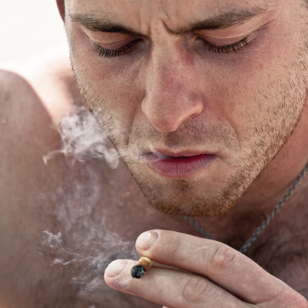 Close up of young man smoking hashish joint. photo