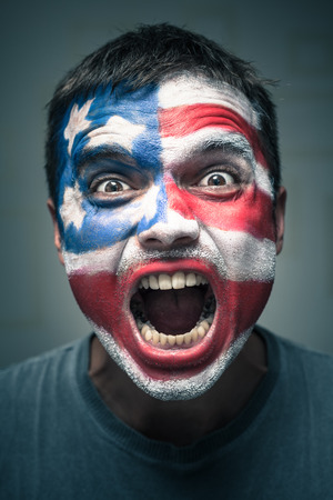 horrifying: Portrait of angry man with USA flag painted on face.