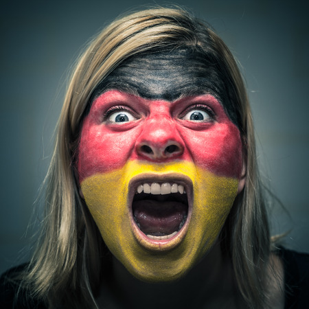 horrifying: Portrait of angry woman with flag of Germany painted on face. Stock Photo