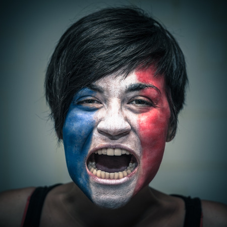 horrifying: Portrait of angry woman with flag of France painted on face. Stock Photo