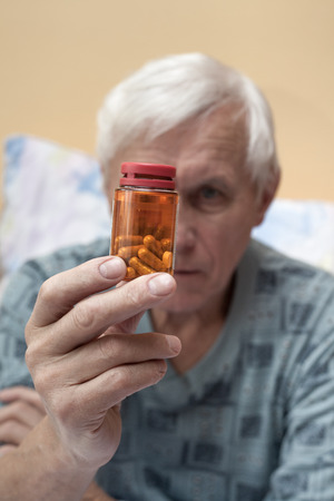 Ill senior man looking at pills. photo