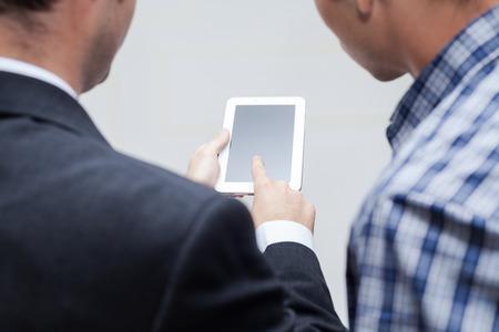 Detail of two businessmen using digital tablet. photo