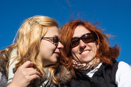 Closeup of two happy girlfriends over blue sky. photo