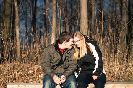 Two young happy people sitting on park bench photo