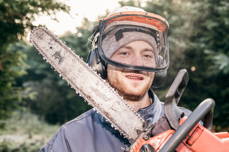 felling: Portrait of professional gardener with chainsaw standing in the garden.