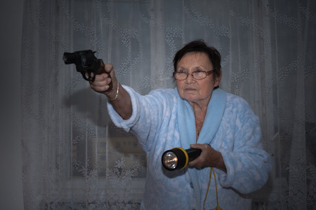 women with guns: Scared senior woman aiming a gun and torch.