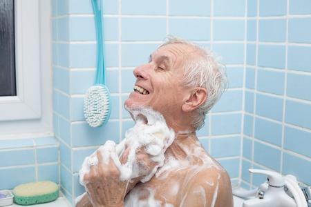 personas banandose: Senior hombre lavar su cuerpo con jabón en el baño.