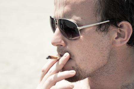 Close up of young man smoking hashish joint.